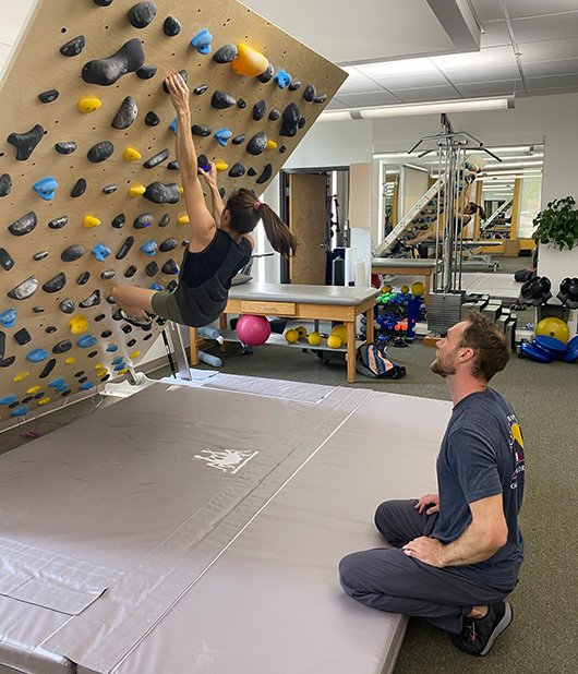 Paige on climbing wall working with Ross